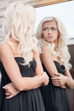 Looking at the mirror. Attractive young blond hair woman in black dress looking at the mirror Stock Image