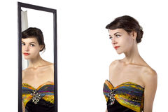 Looking at a Mirror with a Dress. Woman wearing a yellow dress looking at her self in a mirror.  She is trying on a yellow dress Stock Photography
