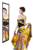 Looking at a Mirror with a Dress. Woman wearing a yellow dress looking at her self in a mirror.  She is trying on a yellow dress Royalty Free Stock Photo