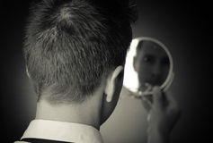 Looking in the mirror and reflecting stock images