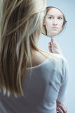 Looking in mirror. Young pretty girl looking at her reflection in mirror Royalty Free Stock Photo