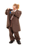 Looking for Money. Beautiful little 7 year old girl in baggy suit looking for money in pocket over white background Royalty Free Stock Photos