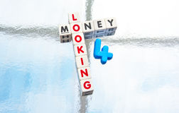 Looking for money. Text 'looking for a money' with uppercase letters inscribed on small white cubes and the blue number 4 replacing 'for', silver background Stock Images