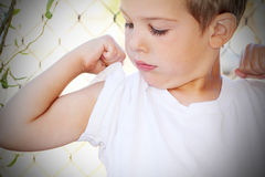 Looking at Muscle. Little blond boy in white tee shirt looking at his arm muscle. Shallow depth of field Royalty Free Stock Photography