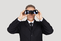 Looking for the new opportunities. Confident mature man in formalwear looking through binoculars while standing against grey background Stock Image