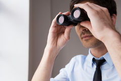 Looking for new opportunities. Confident young man in shirt and tie looking through binoculars Stock Images