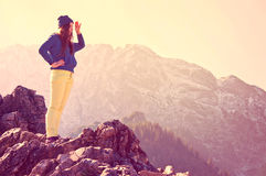 Looking for new opportunities. Young beautiful girl standing on the rocks in mountains and looking for new opportunities. Vintage instagram picture Stock Photo