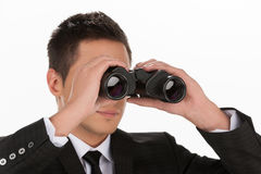 Looking for the new opportunities. Young man in formalwear looking through binoculars while standing isolated on white Stock Image
