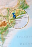 Looking in on New York City, New York. Blue tack on map of Eastern USA with magnifying glass looking in on New York City, New York royalty free stock photo