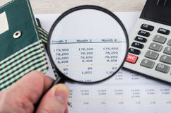 Looking numbers on printout with magnifying glass. Calculator and notepad stock photo
