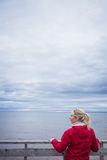 Looking at the Ocean on a cold Autumn Cloudy Day. Lonely Young Woman Looking a the View of the Ocean from an Observatory During a cold Autumn Cloudy Day royalty free stock photography