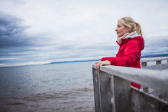 Looking at the Ocean on a cold Autumn Cloudy Day. Lonely Young Woman Looking a the View of the Ocean from an Observatory During a cold Autumn Cloudy Day royalty free stock image
