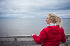 Looking at the Ocean on a cold Autumn Cloudy Day. Lonely Young Woman Looking a the View of the Ocean from an Observatory During a cold Autumn Cloudy Day royalty free stock photos