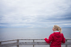 Looking at the Ocean on a cold Autumn Cloudy Day. Lonely Young Woman Looking a the View of the Ocean from an Observatory During a cold Autumn Cloudy Day stock photo