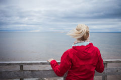 Looking at the Ocean on a cold Autumn Cloudy Day. Lonely Young Woman Looking a the View of the Ocean from an Observatory During a cold Autumn Cloudy Day royalty free stock photo