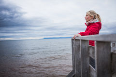 Looking at the Ocean on a cold Autumn Cloudy Day. Lonely Young Woman Looking a the View of the Ocean from an Observatory During a cold Autumn Cloudy Day royalty free stock images