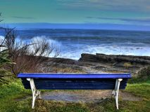 Looking the ocean. Lonely bench to the edge of a cliff stock photography