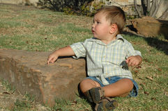 Looking Off. Beautiful Baby boy at the age of 1 sitting outside by a rock in a nature park. Not looking at the camera but over shoulder Royalty Free Stock Photo