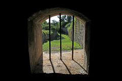 Looking through an Old Jail Window. The view through an old jail window, in an historic fort, with bars blocking an escape Royalty Free Stock Photo