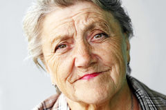 Looking old woman portrait on a grey background.  royalty free stock image