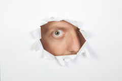 Looking through one eye ... in the paper. Royalty Free Stock Images