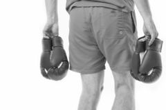Looking for opponent. Man in shorts carries two pairs boxing gloves rear view isolated white background. Equipment stock images