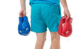 Looking for opponent. Man in shorts carries two pairs boxing gloves rear view isolated white background. Equipment. Professional sportsman. Professional Stock Photo