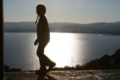 Looking out 2. Little girl silhouetted against lake Royalty Free Stock Photo