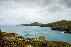 Looking out across the sea, cliffs and hills along the wild Pembrokeshire coast. With dark clouds on a September day. Wales. Looking out across the sea, cliffs stock photos