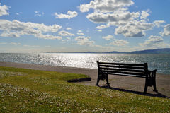 Looking out across the solway. Firth on a bright sunny day with a bench in the foreground Royalty Free Stock Photos