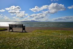 Looking out across the solway. Firth on a bright sunny day with a bench in the foreground Royalty Free Stock Images