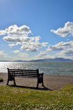 Looking out across the solway. Firth on a bright sunny day with a bench in the foreground Stock Photo