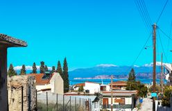 Looking across water to snow covered mountains from steep road in village of Corinth Greece. Looking out across water to snow covered mountains from steep road Royalty Free Stock Images