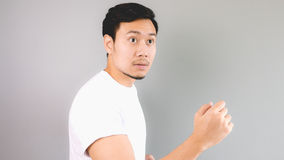 Looking out as he accidently meet someone. An asian man with white t-shirt and grey background stock photo
