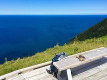 Looking out. Backpack left at the bench looking out at the ocean Royalty Free Stock Photos
