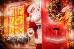 Looking out of the door. Christmas concept. Portrait of a fairytale Santa Claus looks out of the door of his house. Beautiful house decorated for Christmas. Time royalty free stock image