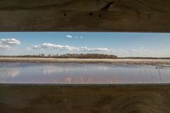 Looking out a duck blind at the beautiful sky, grasslands, and wetlands on a late winter / early spring day in the Crex Meadows Wi. Ldlife Area in Northern royalty free stock image