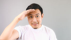 Looking out far with hand covering his face. An asian man with white t-shirt and grey background royalty free stock images