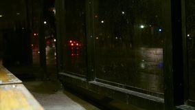 Looking out of a glass bus stop at traffic on rainy evening.  stock video footage