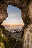 Looking out of a limestone cave to the rising sun on the horizon. Carrick-a-Rede Royalty Free Stock Images