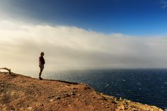 Looking out over the ocean in Madeira. Senior tourist hiking at the coastline cliffs at Ponta de Sao Lourenco on the east coast of Madeira island, with the stock image