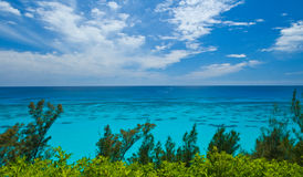 Looking out over a Tropical Ocean, room for text. A tropical ocean, with a clearly visibal reef, against a blue sky with some white clouds Stock Photography