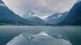 A reflective Fjord. Looking out over the water with a thin layer of mist Royalty Free Stock Image