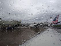 Looking out a rainy window at a American Airplane at Airport. Kauai - April 11, 2018: Looking out a rainy window at a American Airplane at Lihue Airport, Kauai royalty free stock image