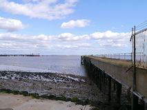 Looking out from shoreline by derelict jetty Stock Photo