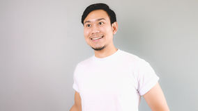 Looking out and smile. An asian man with white t-shirt and grey background stock photos