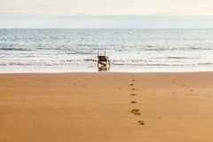 Looking out to sea. Chair at the sea shore looking out to sea. Footprints in the sand Royalty Free Stock Photography
