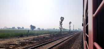 Looking out of the window of a express train of Indian railways with a view of green farm lands.  stock image