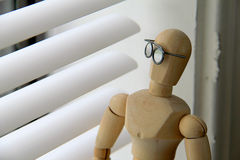 Looking out window on gloomy day. Wooden man with glasses looking out a window on a gloomy, overcast day Stock Photo