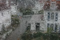 Window with raindrops with buildings behind stock photo